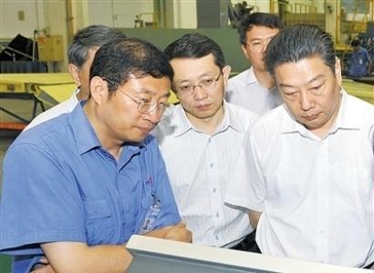 罗阳(左一)在部装厂检查012工程